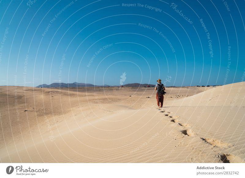 Anonymous man walking on sand hills Man Sand Dune Walking Adventure Desert exploration Sun Traveling footsteps Vacation & Travel Horizon traveler Wilderness