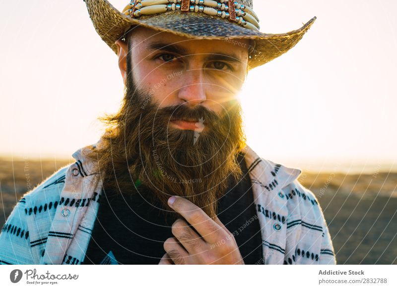 Bearded man in hat against sunlight Man bearded Cowboy Style Sunlight Self-confident Nature Portrait photograph Hat Countries Masculine Earnest Straw hat outfit