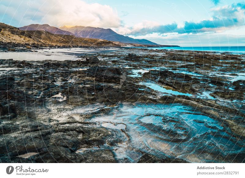 Amazing shoreline formations with mountains on background Coast Mud Formation Ocean Landscape Muddy Rock Wilderness Beauty Photography Peaceful Beach Natural