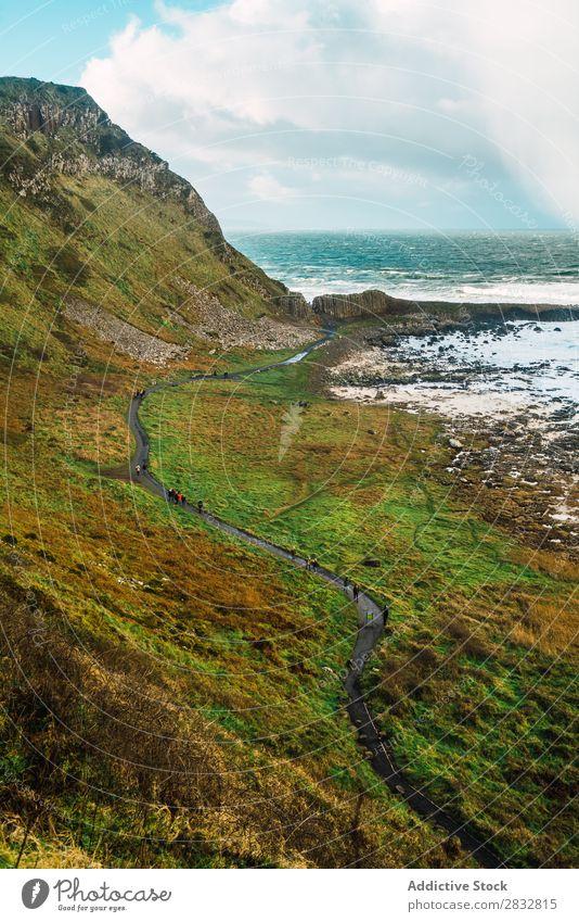 Small road on hill at seaside Coast Rock Street Asphalt Ocean Landscape Beach Nature Water Natural seascape Stone Beautiful Green Grass Northern Ireland