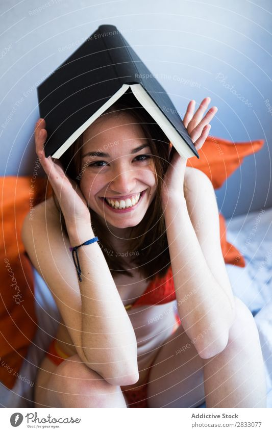 Cheerful girl posing with book Girl Posture Bed Book Creativity on head Joy Underwear Morning Bedroom Laughter Funny Sit Safety (feeling of) Smiling Relaxation