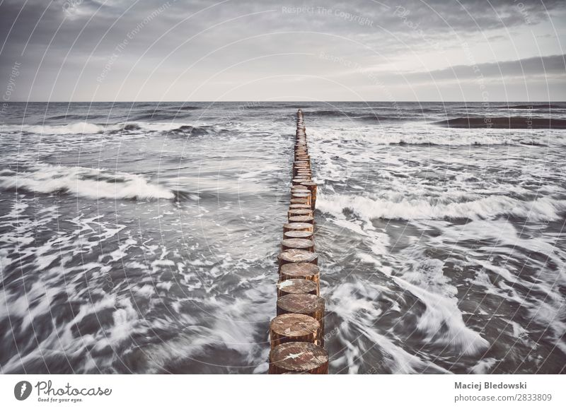 Color toned picture of a wooden breakwater Vacation & Travel Far-off places Freedom Beach Ocean Island Waves Nature Sky Clouds Horizon Storm Wind Gale Sadness