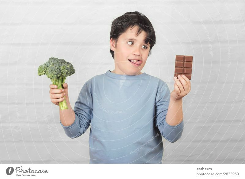 Hungry child with broccoli and an chocolate bar in his hands Food Vegetable Dessert Chocolate Nutrition Eating Vegetarian diet Diet Lifestyle Joy Overweight