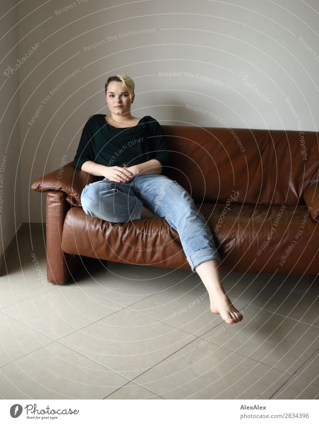 Young woman sitting on the couch Style Contentment Sofa Room Youth (Young adults) 18 - 30 years Adults Jeans Piercing Barefoot Blonde Short-haired Sit Esthetic