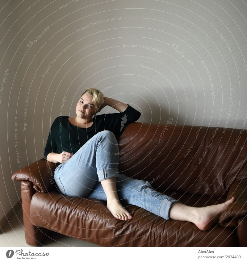 Young woman sitting on the couch Style Joy Beautiful Contentment Sofa Room Youth (Young adults) 18 - 30 years Adults Jeans Barefoot Blonde Short-haired Looking