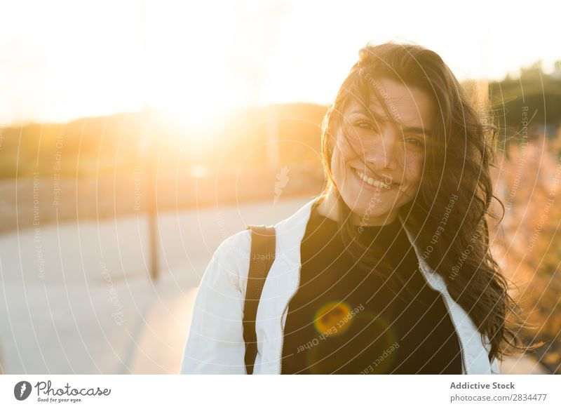 Smiling adorable female in sunlight Woman Posture Hipster Portrait photograph Style To enjoy waving hair Town Cheerful Brunette Self-confident Laughter