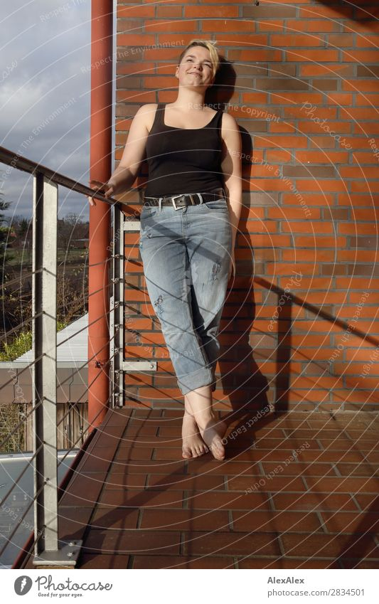 Young woman on sunny balcony Joy Beautiful Well-being Balcony Youth (Young adults) Barefoot 18 - 30 years Adults Jeans Blonde Short-haired Territory Smiling