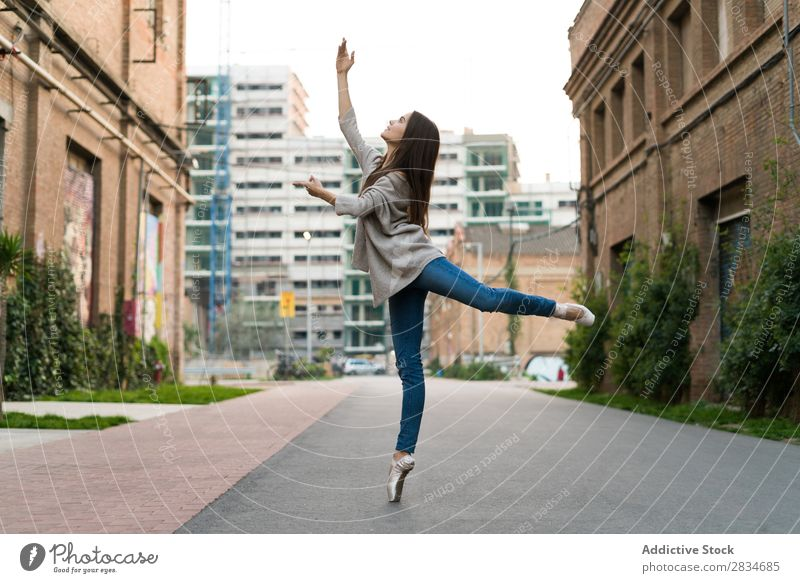 Horizontal outdoors shot of a woman in the street performing a ballet. dance concept city urban girl female dancer ballerina elegance beautiful performance