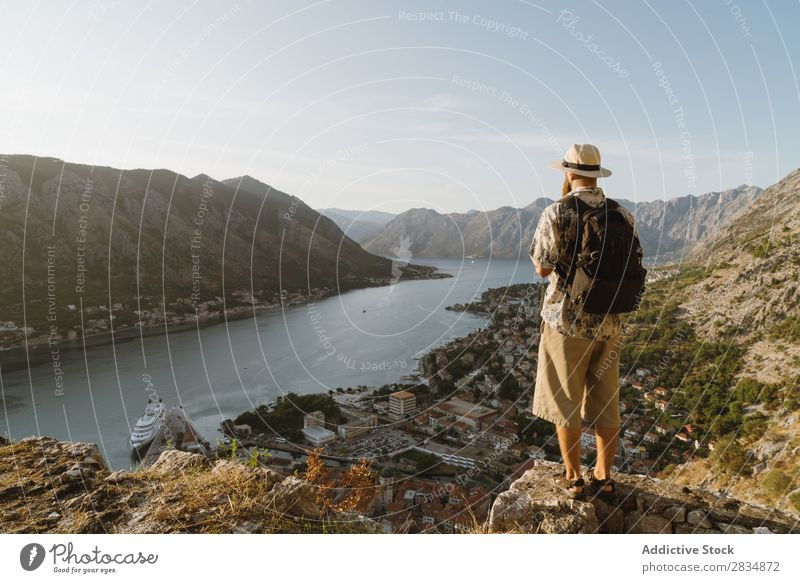 Tourist looking at riverside town Town Mountain River Man Human being Village Vantage point