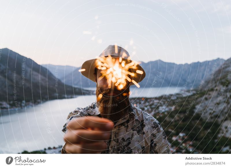 Man with sparkler in mountains Town Mountain River Human being Tourist Sparkler firework Festive Guest bearded Village Vantage point pathway Landscape