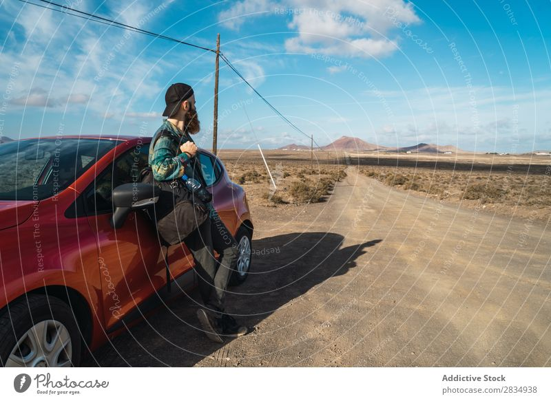 Tourist leaning on car roof Car Mountain Drive Red Stand Lean Nature Street Landscape Natural Rock Stone Lanzarote Spain Vantage point Vacation & Travel Tourism