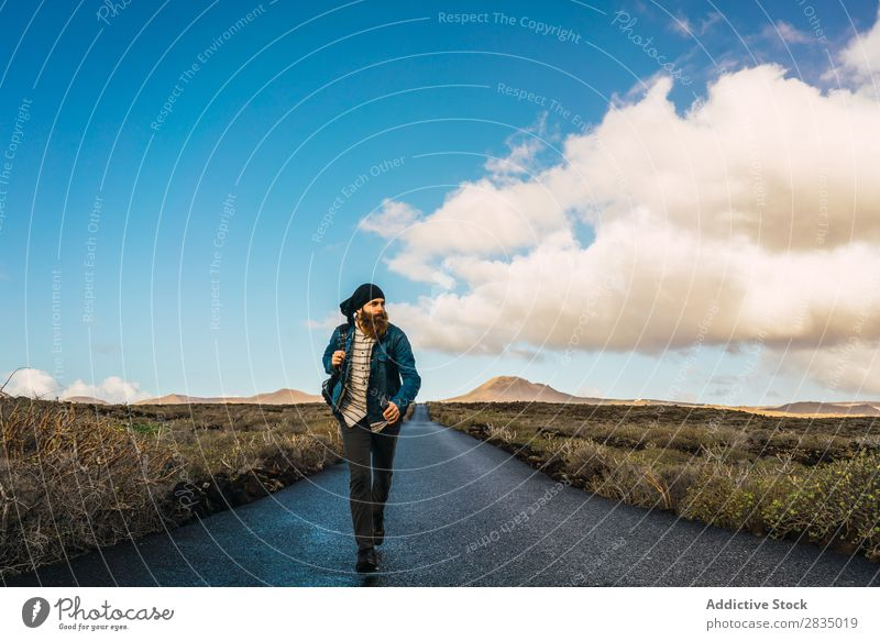 Man walking on road in field Tourist Field Walking Mountain Dry Clouds Nature Landscape Natural Rock Stone Lanzarote Spain Vantage point Vacation & Travel