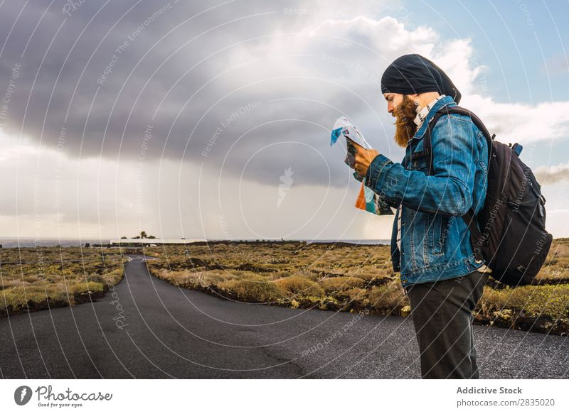 Tourist man with map Field Map Navigation Lost Backpack Stand Rest Clouds Nature Landscape Natural Lanzarote Spain Vantage point Vacation & Travel Tourism Trip