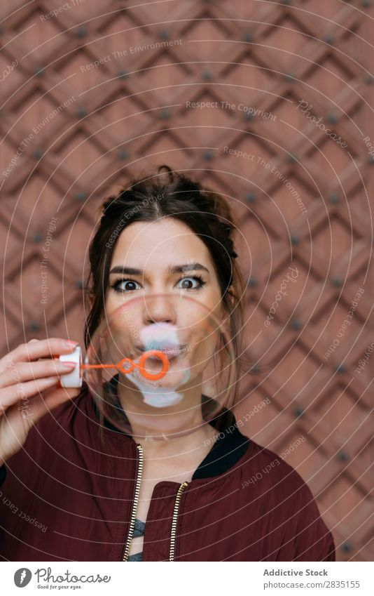 Surprised woman blowing bubbles Bubble Blow Woman surprised Brick Easygoing Wall (building) Happy Human being Hold Caucasian Youth (Young adults) Adults