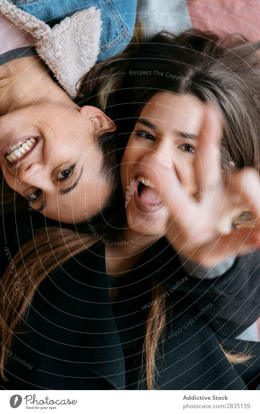Happy women couple looking at camera Gesture two fingers lay Couple Woman Homosexual Alternative Love Human being Caucasian Youth (Young adults) Relationship