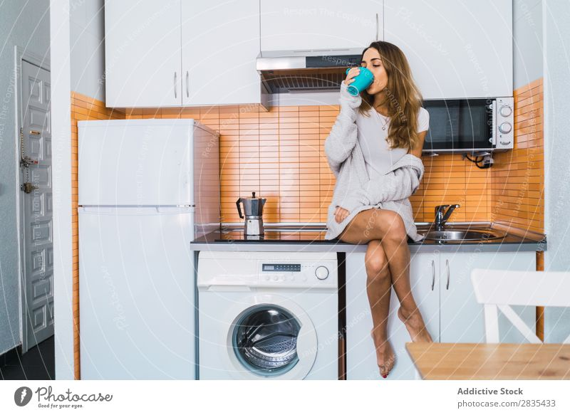 Woman having hot drink on kitchen pretty Home Youth (Young adults) Coffee Cup Drinking Sit brewed Posture Portrait photograph Beautiful Lifestyle