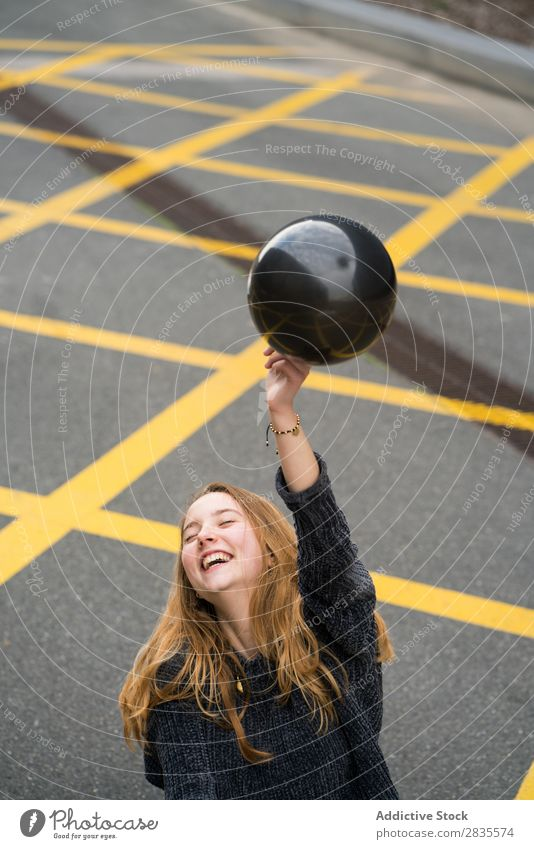 Young girl in Barcelona woman pretty balloon black laughing cheerful mouth opened parking lot lines ground yellow portrait young beautiful hair female sweater