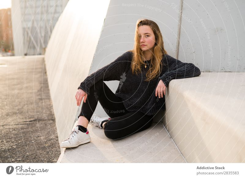 Outdoors portrait of young girl on concrete stairs looking at camera. woman sitting block building dreamy thoughtful pensive pretty beautiful female sweater