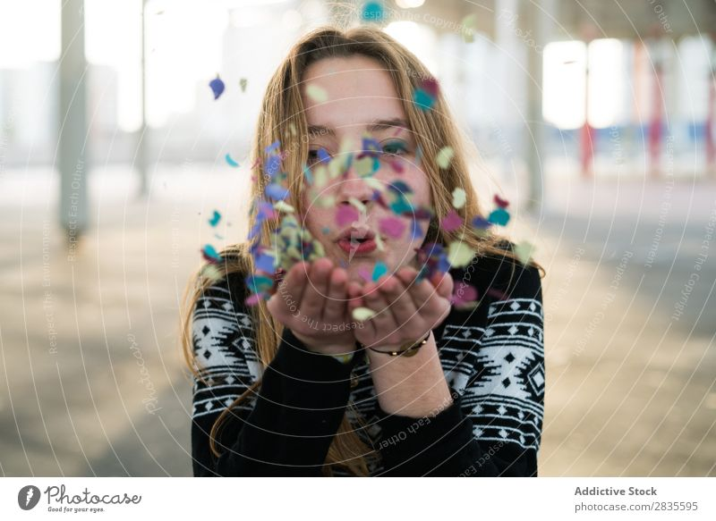 Woman blowing the confetti Blow Confetti Joy Hand Multicoloured Looking into the camera Bright pretty Stand Flying Hair Cheerful Happy Smiling Happiness