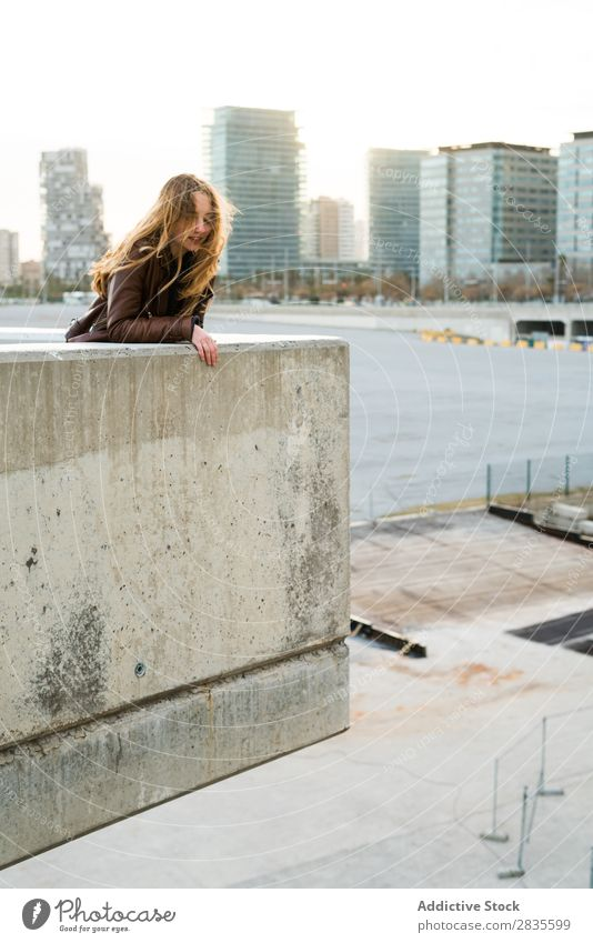 Woman leaning on a block Concrete Block Lean Town Street City Building Dream Smiling Flying Hair Considerate Pensive pretty Youth (Young adults) Beautiful
