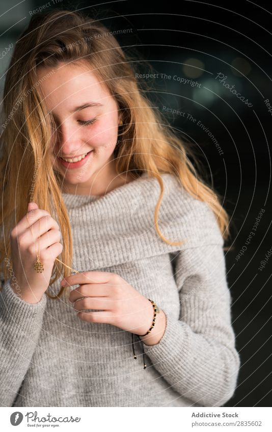 Vertical portrait of young woman touching her necklace. pretty beautiful looking down sensual female dreamy thoughtful collar pensive sweater casual face girl