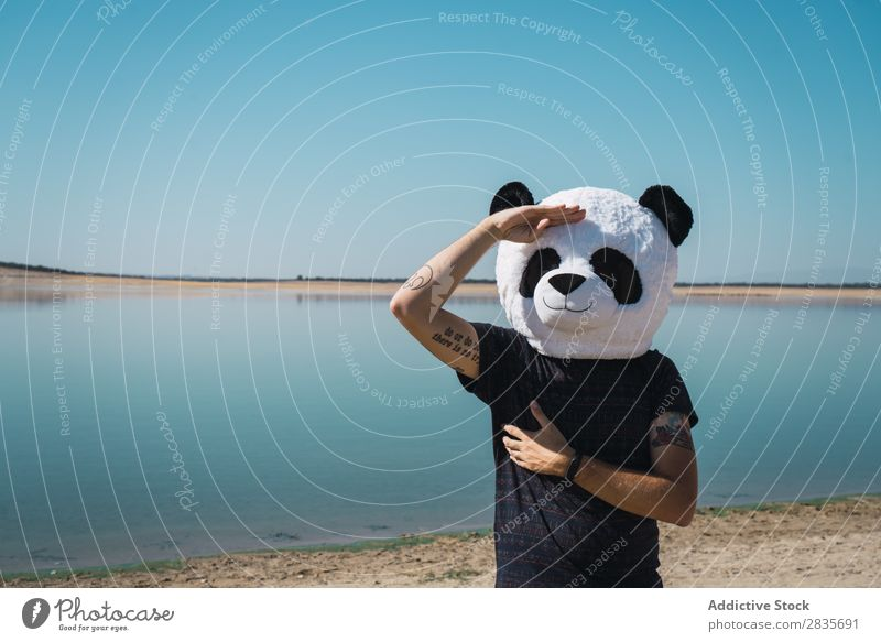 Traveler in creative hat posing on lake Man Discovery Panda Costume Traveling Nature Expedition Hat Tourism gesturing Wanderlust Creativity Wear having fun