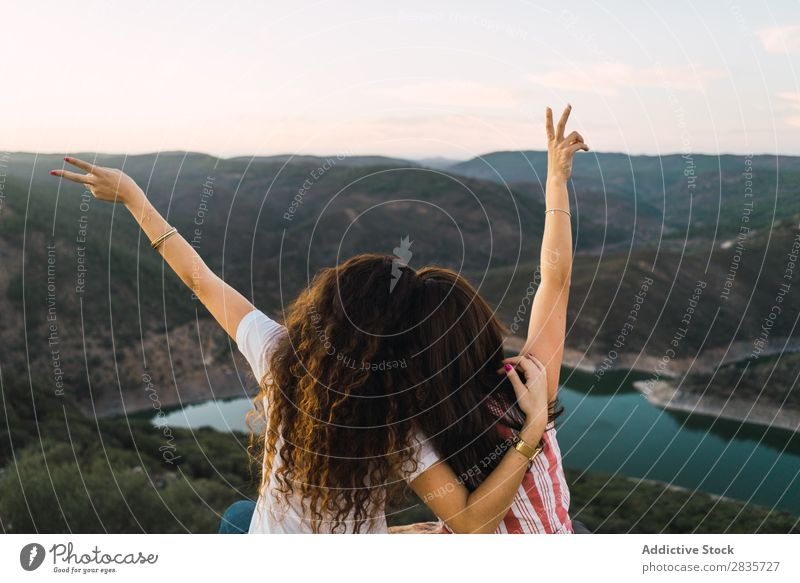 Stylish women sitting on rock in breathtaking landscape Woman Nature Mountain Point in time Cheerful Panorama (Format) Summer Wanderlust having fun Posture