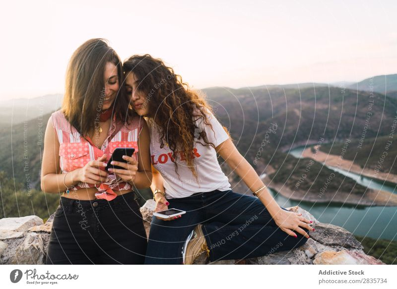 Stylish women browsing phone on breathtaking landscape Woman Nature Mountain Point in time Cheerful Panorama (Format) Summer PDA Wanderlust having fun Posture