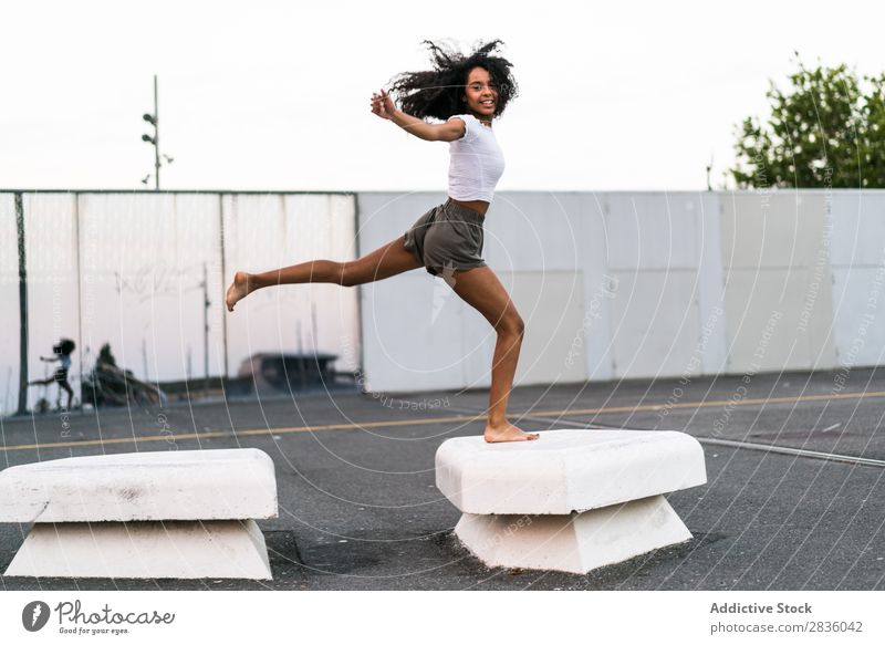 Cheerful woman jumping Woman pretty Youth (Young adults) Jump Athletic blocks Concrete gymnastic Happy Portrait photograph Looking into the camera Black African