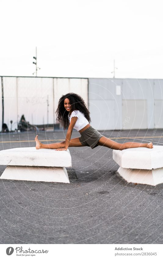Happy woman doing string Woman pretty Youth (Young adults) String Sit Gymnastics City Town Concrete blocks Smiling Cheerful Portrait photograph