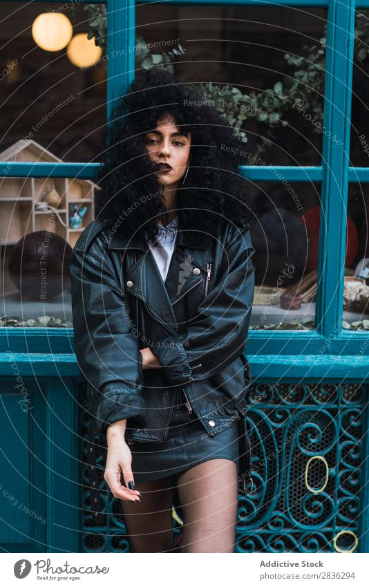 Pretty woman posing at case Woman Attractive City fashionable Curly Brunette Jacket Stand To fall Glass Fashion Youth (Young adults) Beautiful pretty Street
