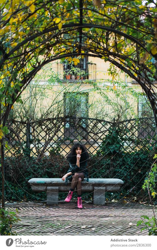 Woman on fence in park Attractive City fashionable Curly Fence Park Brunette Jacket Fashion Youth (Young adults) Beautiful pretty Street Model Style Hair