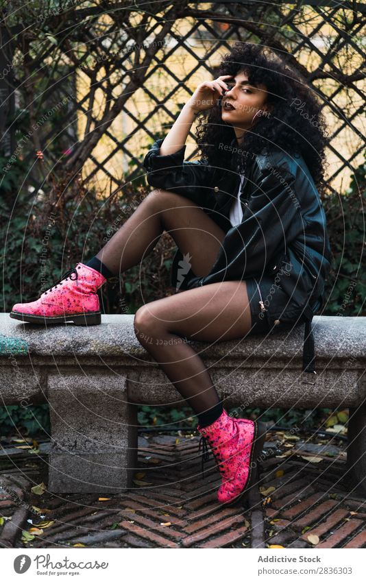 Woman on fence in park Attractive City fashionable Curly Fence holding hair Park Brunette Jacket Fashion Youth (Young adults) Beautiful pretty Street Model