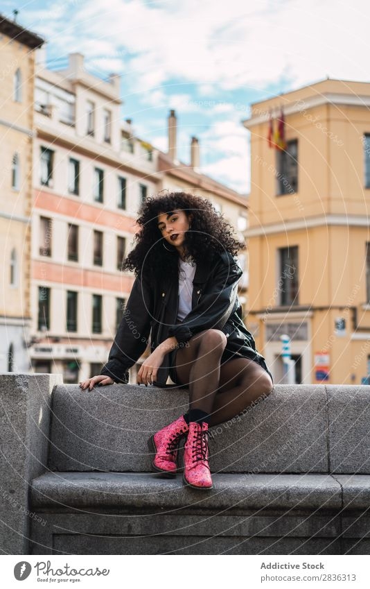 Pretty woman sitting on fence Woman Attractive City fashionable Curly Brunette Jacket Fence Fashion Youth (Young adults) Beautiful pretty Street Model Style