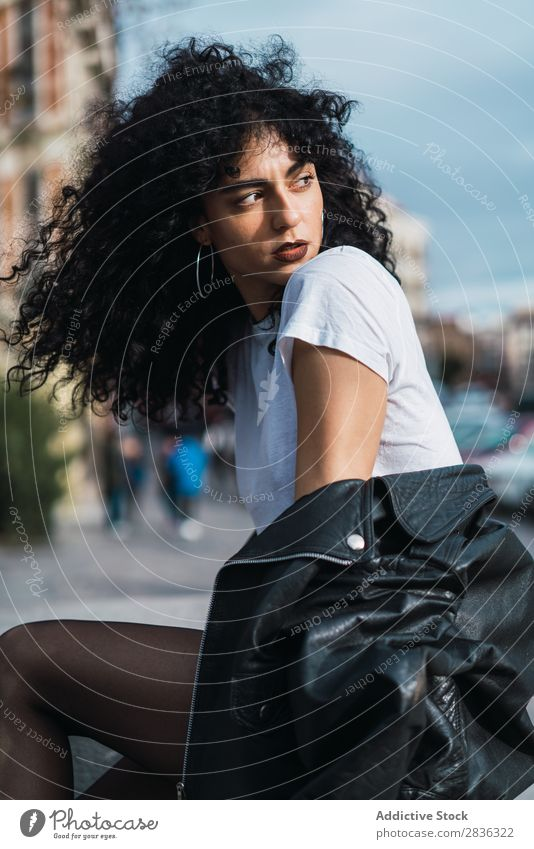 Curly woman posing in city Woman Attractive City fashionable Brunette Looking away Jacket Fence Fashion Youth (Young adults) Beautiful pretty Street Model Style