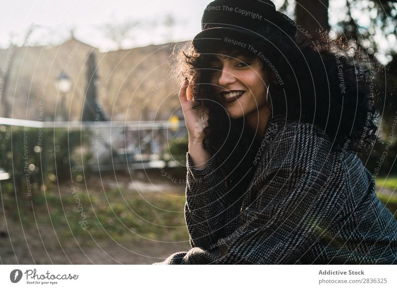 Young stylish woman sitting in city Woman Attractive City fashionable Curly Brunette Coat Hat Sit Fence Vantage point Fashion Youth (Young adults) Beautiful