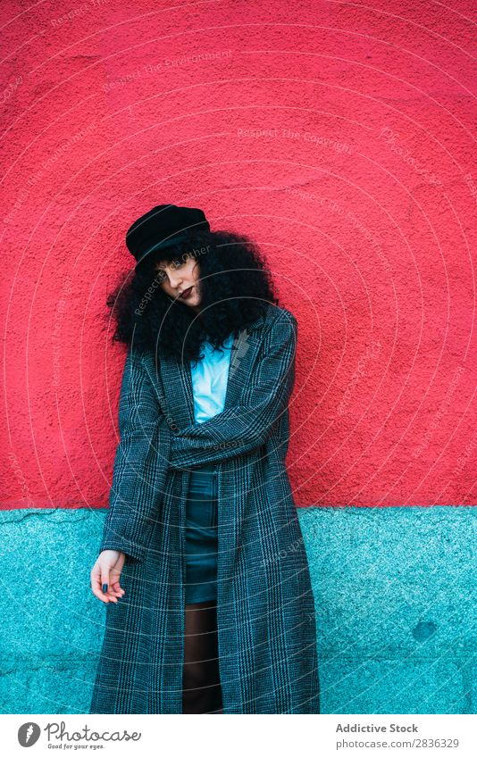Stylish curly woman at colorful wall Woman Attractive City fashionable Curly Brunette Wall (building) Multicoloured Red Bright Looking into the camera Coat