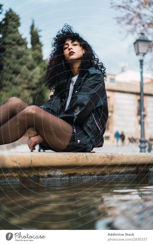 Young woman posing at fountain Woman Attractive City fashionable Curly Brunette Jacket Fountain Water Looking into the camera Fashion Youth (Young adults)