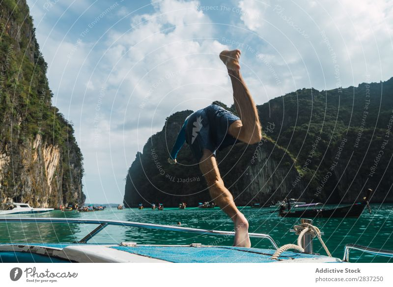Man jumping from boat Watercraft Jump Ocean Dive Vacation & Travel Joy Summer Youth (Young adults) Yacht Adventure Cruise Sail Sailboat Sunbeam Rock