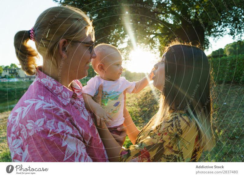 Happy lesbian couple with child Mother Child Park Green Sunbeam Human being Woman Happiness Summer Lifestyle Love same gender parents Homosexual Couple