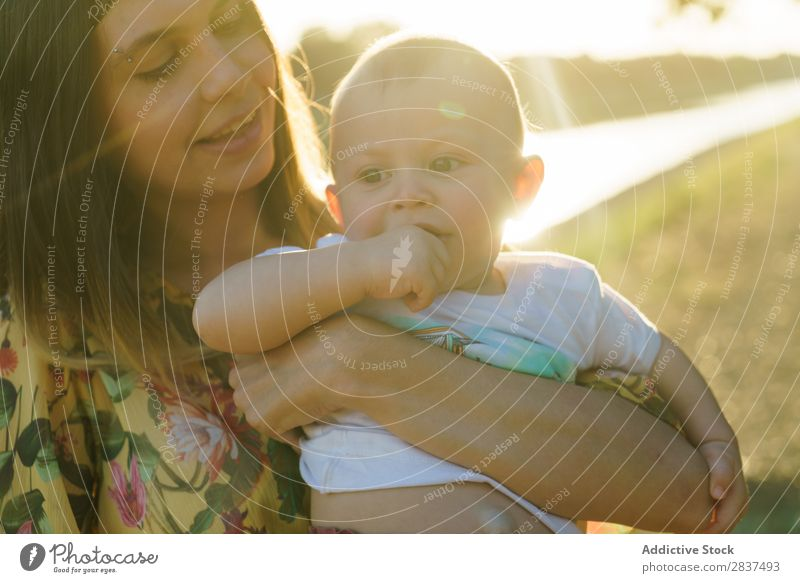 Mother holding kid on hands in park Child Park Sunbeam Family & Relations Happy Human being Woman Happiness Summer Lifestyle Love Parents Nature