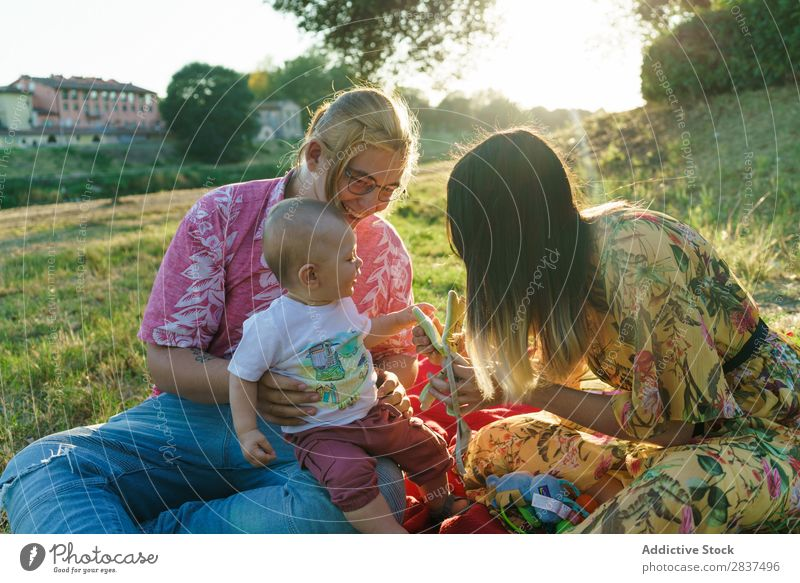 Happy family in park Mother Child Park Lawn Green Sunbeam Human being Woman Happiness Summer Lifestyle Love same gender parents Homosexual Couple