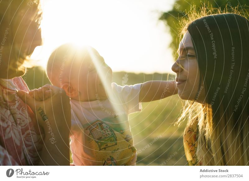 Happy family with child Mother Child Park Green Carrying Sunbeam Human being Woman Happiness Summer Lifestyle Love same gender parents Homosexual Couple