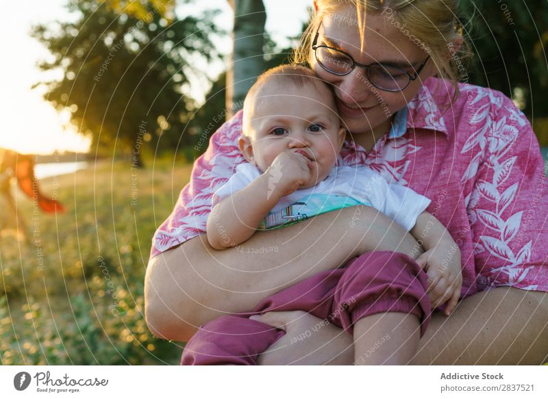 Mother sitting with kid on hands Child Park Lawn Green Sunbeam Family & Relations Happy Human being Woman Happiness Summer Lifestyle Love Parents Nature