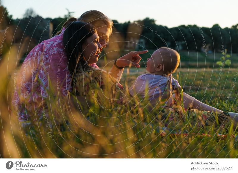 Happy lesbian family with child Mother Child Park Lawn Green Sunbeam Human being Woman Happiness Summer Lifestyle Love same gender parents Homosexual Couple