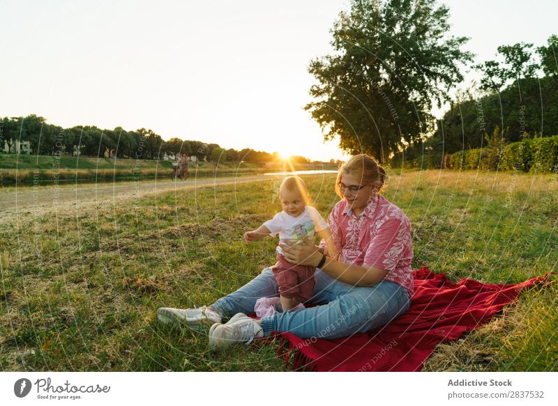 Woman with child on lawn Mother Child Park Lawn Green Sunbeam Happy Human being Happiness Summer Lifestyle Love same gender parents Homosexual Couple