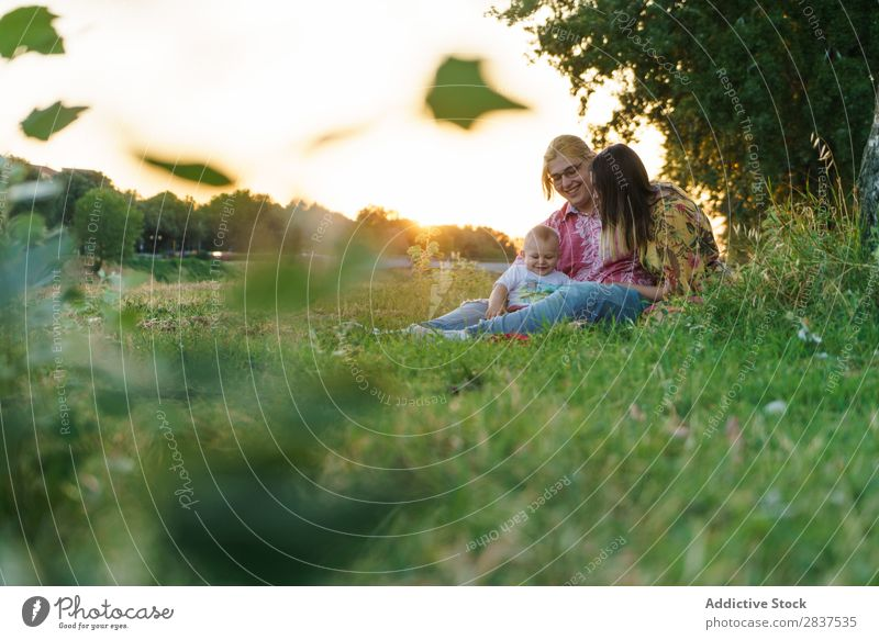Lesbian family with child on lawn Mother Child Park Lawn Green Sunbeam Happy Human being Woman Happiness Summer Lifestyle Love same gender parents Homosexual