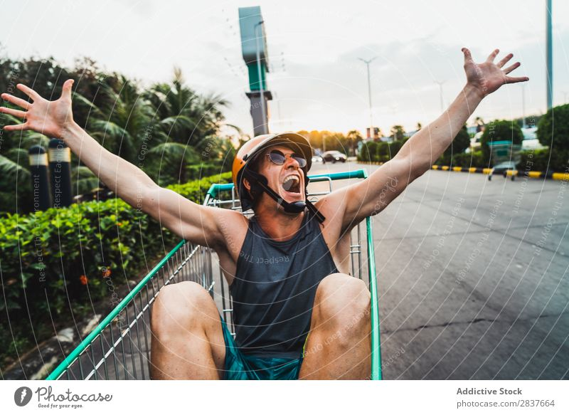 Emotional man in shopping cart Man Shopping Trolley riding Cart pushcart Sunglasses shopper Ride handsome Cheerful Joy Parking lot Human being Markets Humor