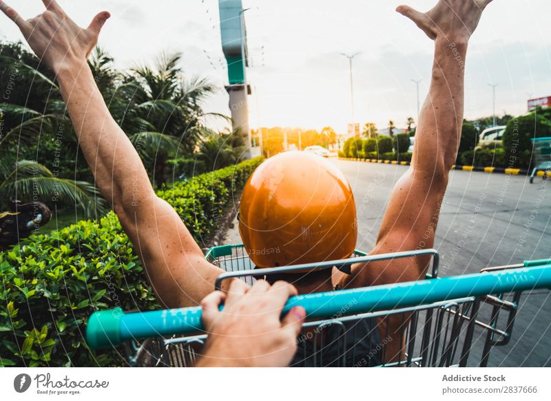 Man riding in shopping cart Shopping Trolley Cart pushcart shopper Ride handsome Cheerful Joy Parking lot Human being Pushing Markets Humor Carriage Happy