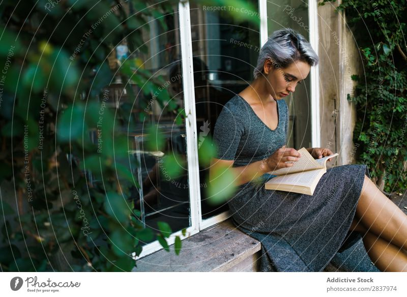 Woman reading book at window Book Street Sit Window Windowsill Beautiful Girl Youth (Young adults) Student pretty Adults Smiling City Beauty Photography